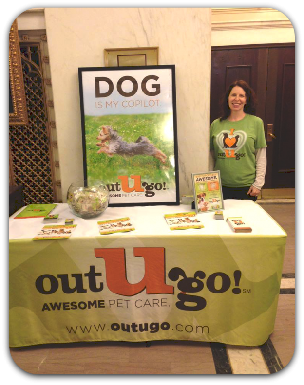 Out-U-Go! Chicago General Manager Sara stands at our event table talking to Village Green's Fisher Building residents about their pet care needs!